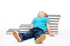 Kid tiered of education. Lay exhausted on the floor and steps made of books Stock Photos