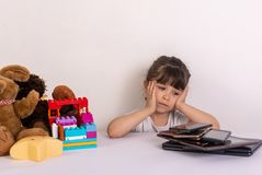 Kid tired because of too much information. Stressed little girl sitting near phones, smartphones, laptops, pc tablets. Concept of information overload royalty free stock photography