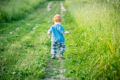 Kid toddler on a countryside road, back view. Kid toddler on a countryside road and meadow field around Stock Image