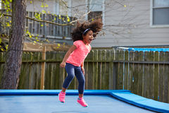Kid toddler girl jumping on a trampoline stock photography