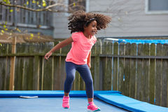 Kid toddler girl jumping on a trampoline Royalty Free Stock Photos