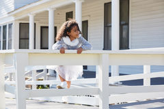 Kid toddler girl playing climbing a fence outdoor Royalty Free Stock Photo