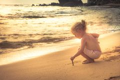 Kid toddler girl writing on sand beach surf during summer holidays concept happy childhood travel lifestyle. Kid toddler girl writing on sand beach surf during stock photography