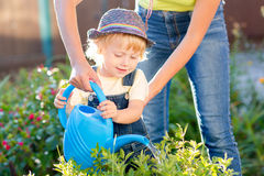 Kid toddler helping mother in the garden sunny summertime Royalty Free Stock Photography