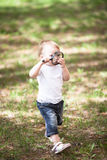 Kid Toddler with magnifying glass outside stock photo