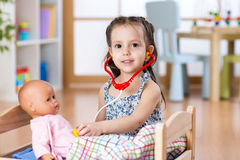 Kid toddler playing doctor role game examining her doll using stethoscope sitting in playroom at home, school or Stock Photos