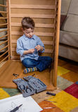 Kid with tools assembling a new furniture. Portrait of cute kid assembling with tools a new furniture for home. Family leisure concept Stock Photography