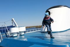 Kid on top deck of ship. Kid running on top deck of ship royalty free stock images