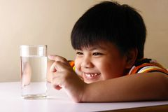 Kid touching a glass of water on a wooden table Royalty Free Stock Images