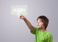 Kid touching LEARN button. On a touchscreen Royalty Free Stock Images