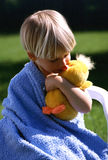 Kid with a toy. A boy sitting on a plastic chair kissing plush duckling Stock Images