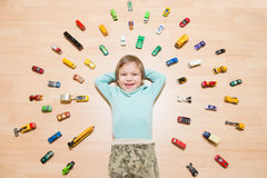 Kid with toy cars around him Royalty Free Stock Images
