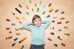 Kid with toy cars around him Royalty Free Stock Image