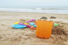 Kid toys on sandy beach. Kid toys and sandals on sandy beach Stock Image
