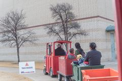 Kid trackless train ride in public winter event in Irving, Texas. Unidentified kids and parents riding on trackless train ride wagon. Train crossing sign at Stock Photos