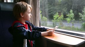 Kid Traveling by Train. Cute boy traveling by train looking through window and holding the tickets stock video