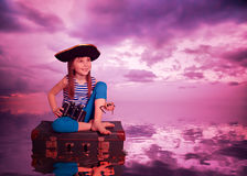 The kid travels on the sea and on the suitcase. Stock Photo