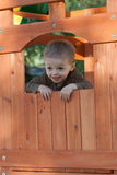 Kid in treehouse. Boy hanging out of window in cedar treehouse swingset Royalty Free Stock Photo