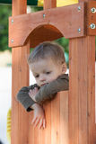 Kid in treehouse. Boy hanging out of window in cedar treehouse swingset Stock Photography