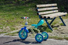 Kid tricycle in the park. With bench in background Stock Photos
