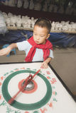 Kid turning wheel for fortune. Chinese kid turning wheel for fortune in countryside Stock Images