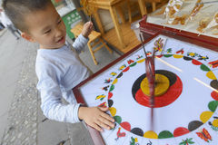 Kid turning wheel for fortune. Chinese kid turning wheel for fortune in countryside Royalty Free Stock Photos