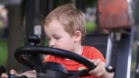 Kid turns the wheel of the tractor Royalty Free Stock Photo