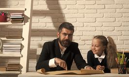 Kid and tutor with smiling faces. Girl and man. Kid and tutor with smiling faces. Girl and men sit at desk and read map. Classroom and alternative education Stock Photos