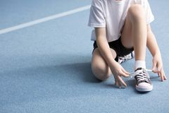 Kid tying a shoe. Close-up of kid tying a shoe on blue floor at the gym royalty free stock photo