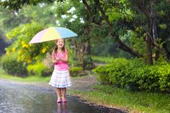 Kid with umbrella playing in summer rain. Kid playing out in the rain. Children with umbrella play outdoors in heavy rain. Little girl caught in first spring Royalty Free Stock Images
