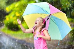 Kid with umbrella playing in summer rain. Kid playing out in the rain. Children with umbrella play outdoors in heavy rain. Little girl caught in first spring Stock Images