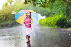 Kid with umbrella playing in summer rain. Kid playing out in the rain. Children with umbrella play outdoors in heavy rain. Little girl caught in first spring Stock Photos