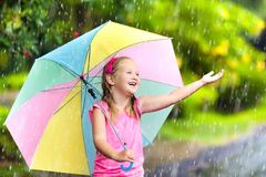 Kid with umbrella playing in summer rain. Kid playing out in the rain. Children with umbrella play outdoors in heavy rain. Little girl caught in first spring Royalty Free Stock Photo