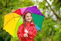 Kid with umbrella playing in summer rain