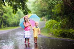 Kid with umbrella playing in summer rain. Kids playing out in the rain. Children with umbrella play outdoors in heavy rain. Little girl and boy caught in first Royalty Free Stock Photos