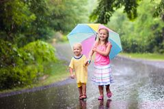 Kid with umbrella playing in summer rain. Kids playing out in the rain. Children with umbrella play outdoors in heavy rain. Little girl and boy caught in first Royalty Free Stock Photography
