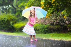 Kid with umbrella playing in summer rain. Kid playing out in the rain. Children with umbrella play outdoors in heavy rain. Little girl caught in first spring Stock Photography