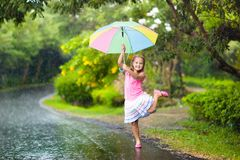 Kid with umbrella playing in summer rain. Kid playing out in the rain. Children with umbrella play outdoors in heavy rain. Little girl caught in first spring Stock Photo