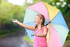Kid with umbrella playing in summer rain. Kid playing out in the rain. Children with umbrella play outdoors in heavy rain. Little girl caught in first spring Royalty Free Stock Image