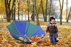 The kid with an umbrella plays in autumn park Stock Images