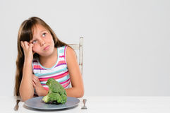 Kid unhappy with her vegetables Stock Photos