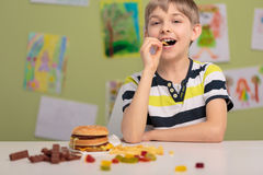Kid and unhealthy snacks. Cheerful kid at school eating unhealthy snacks stock images