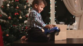 Kid unpacking gift on table. Toy and candies for present. Best presents for Christmas. Happy holidays guaranteed stock video