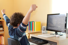 Kid using computer. Young boy using computer at home Stock Photo