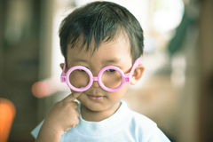 Kid using doctor glass toy Royalty Free Stock Images