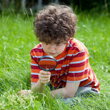 Kid using magnifying glass Stock Images