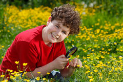 Kid using magnifying glass Stock Photos