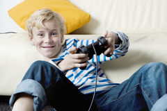 Kid using playstation controls at home. Royalty Free Stock Images