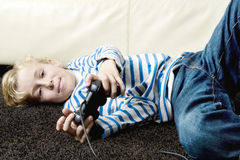 Kid using playstation controls at home. Royalty Free Stock Photos