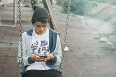 Kid using smartphone on swing Stock Images